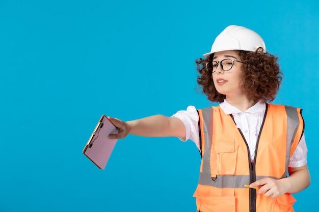 Vooraanzicht vrouwelijke bouwer in uniform controlerend werk op blauw