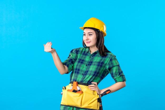 Vooraanzicht vrouwelijke bouwer in uniform en helm die iemand op blauw roept