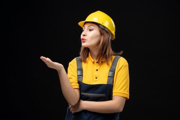 Vooraanzicht vrouwelijke bouwer in uniform en helm die kussen stuurt naar iemand op zwarte muur