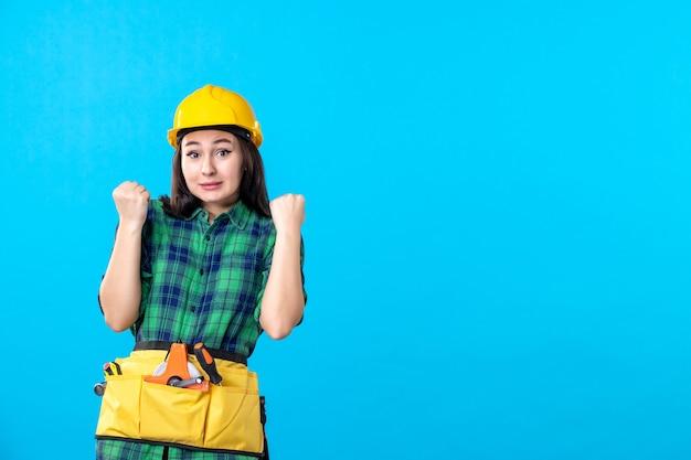 Vooraanzicht vrouwelijke bouwer in uniform en helm die zich verheugt op blauw