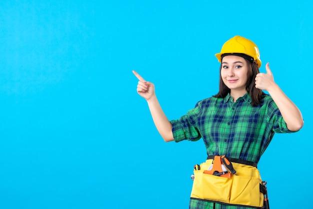 Vooraanzicht vrouwelijke bouwer in uniform en helm glimlachend op blauw