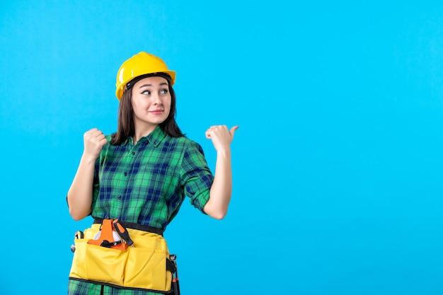 Vooraanzicht vrouwelijke bouwer in uniform en helm op blauw