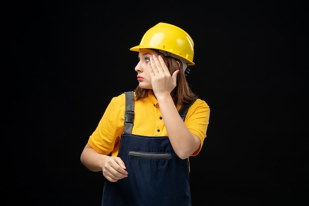 Vooraanzicht vrouwelijke bouwer in uniform en helm op de zwarte muur