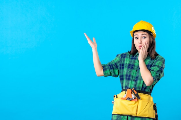 Vooraanzicht vrouwelijke bouwer in uniform en helm verrast op blauw