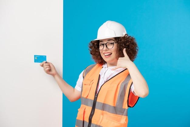 Vooraanzicht vrouwelijke bouwer in uniform met blauwe creditcard in haar handen op blauw