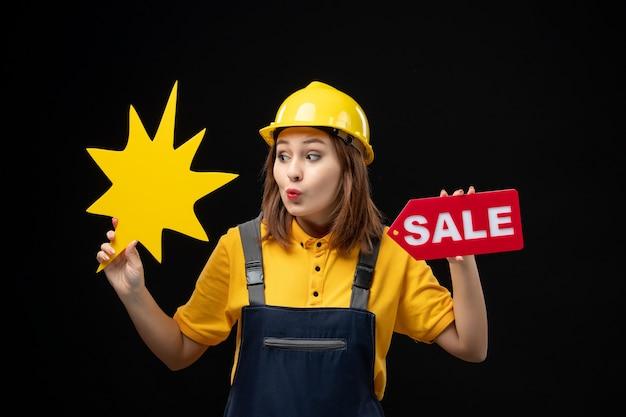 Vooraanzicht vrouwelijke bouwer in uniform met gele figuur en verkoop op een zwarte muur
