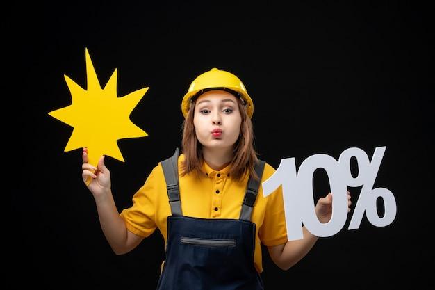 Vooraanzicht vrouwelijke bouwer in uniform met gele figuur op de zwarte muur