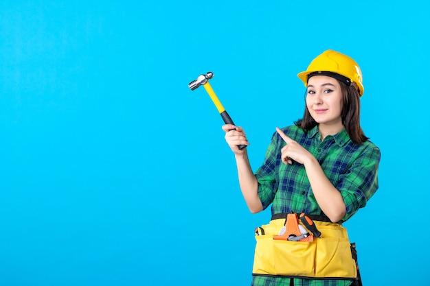 Vooraanzicht vrouwelijke bouwer in uniform met hamer op blauw