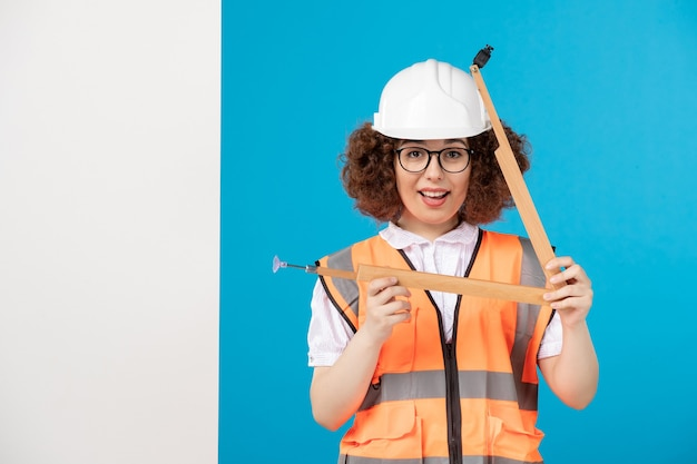 Vooraanzicht vrouwelijke bouwer in uniform met houten gereedschap op blauw