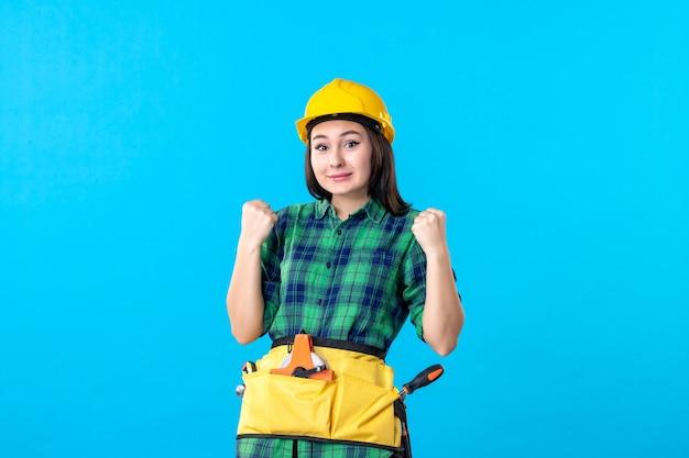 Vooraanzicht vrouwelijke bouwer in uniform met verschillende tools op blauw