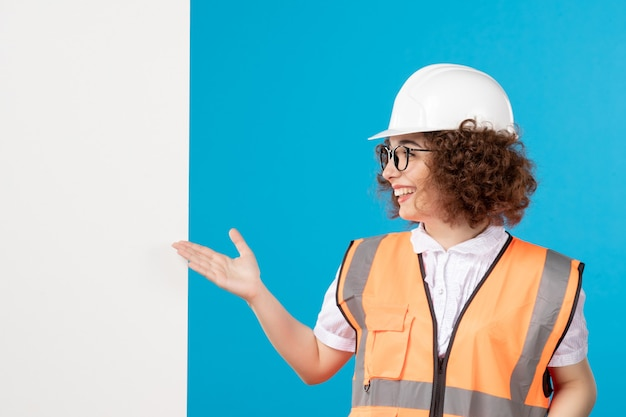 Vooraanzicht vrouwelijke bouwer in uniform op het blauw