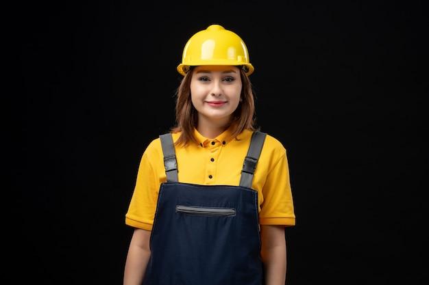 Vooraanzicht vrouwelijke bouwer in uniforme en beschermende helm op zwarte muur