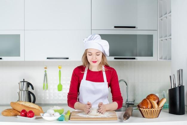 Vooraanzicht vrouwelijke chef-kok die het deeg in de keuken kneedt
