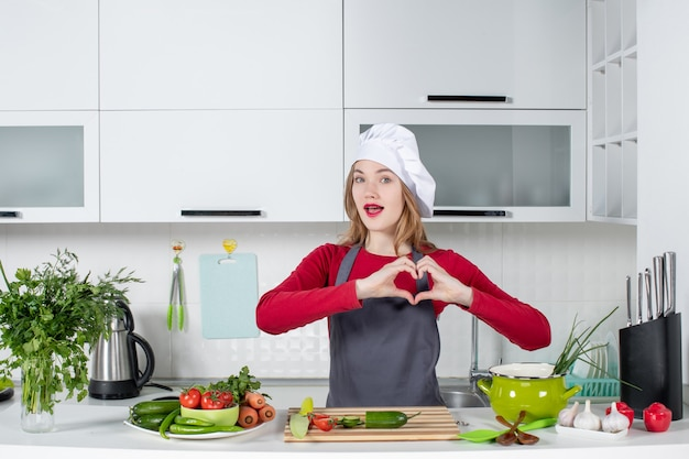Vooraanzicht vrouwelijke chef-kok die in kokhoed hartteken maakt