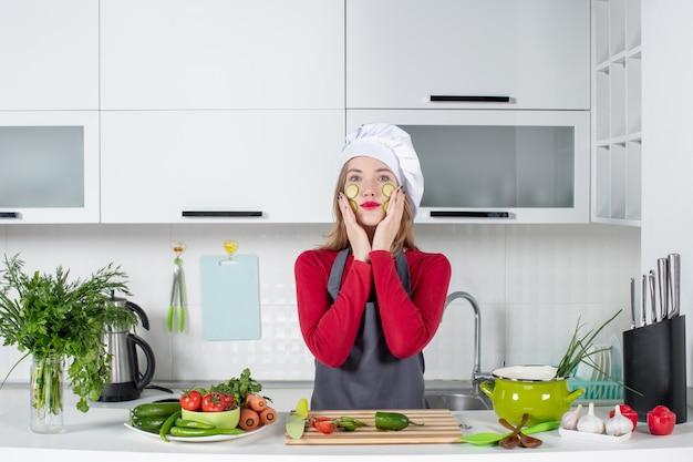 Vooraanzicht vrouwelijke chef-kok die plakjes komkommer op haar gezicht zet