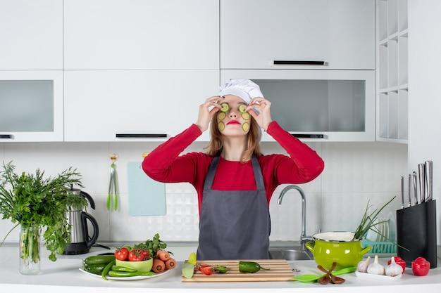 Vooraanzicht vrouwelijke chef-kok die plakjes komkommer op haar ogen zet