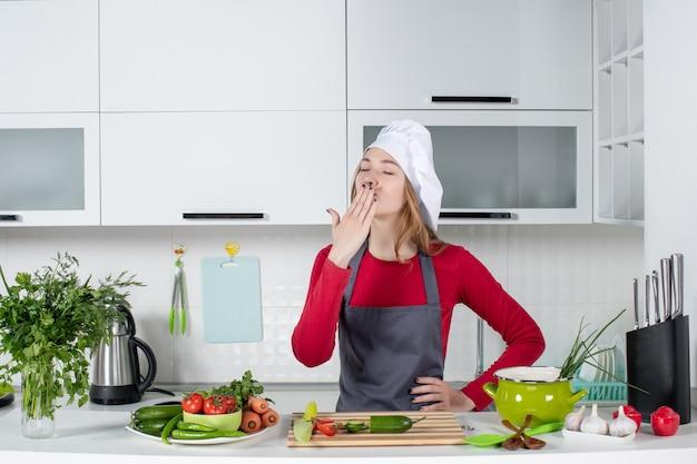 Vooraanzicht vrouwelijke chef-kok in kok hoed blaast kus in de keuken
