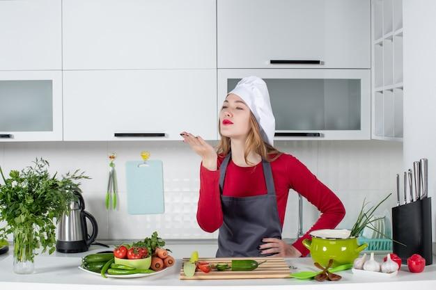 Vooraanzicht vrouwelijke chef-kok in kok hoed blazende kus