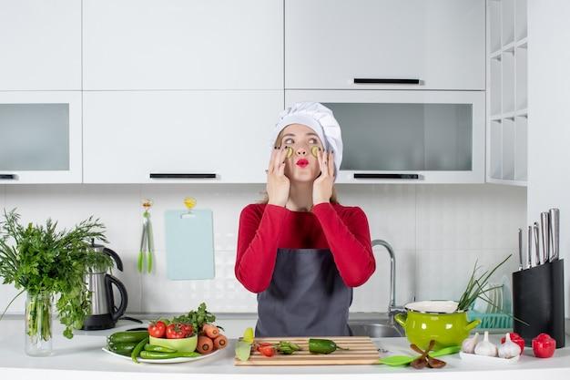 Vooraanzicht vrouwelijke chef-kok in kok hoed die plakjes komkommer op haar gezicht in de keuken zet
