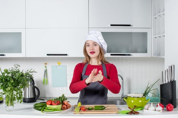 Vooraanzicht vrouwelijke chef-kok in kok hoed handen klappen