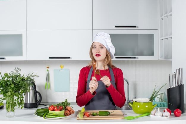 Vooraanzicht vrouwelijke chef-kok in kok hoed met houten lepels spoon