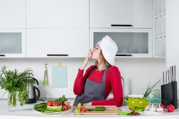 Vooraanzicht vrouwelijke chef-kok in kokshoed die kus verzendt