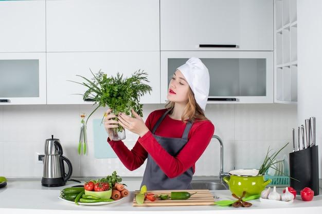 Vooraanzicht vrouwelijke chef-kok in koksmuts die groenten in fles omhoog houdt