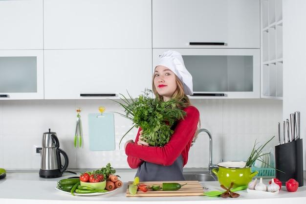 Vooraanzicht vrouwelijke chef-kok in koksmuts die groenten omhoog houdt