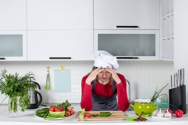 Vooraanzicht vrouwelijke chef-kok in koksmuts die haar hoofd vasthoudt