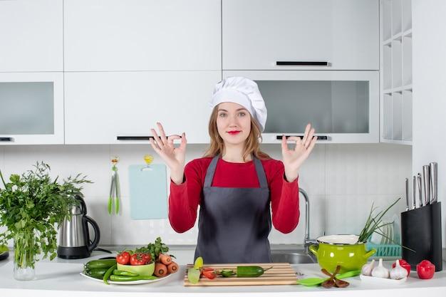 Vooraanzicht vrouwelijke chef-kok in koksmuts die okey teken maakt