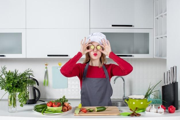 Vooraanzicht vrouwelijke chef-kok in koksmuts die plakjes komkommer op haar gezicht zet in moderne keuken