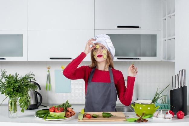 Vooraanzicht vrouwelijke chef-kok in koksmuts die plakjes komkommer op haar gezicht zet