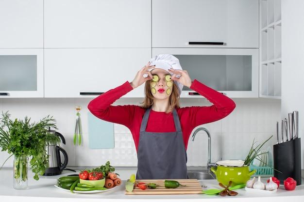 Vooraanzicht vrouwelijke chef-kok in koksmuts die plakjes komkommer op haar ogen zet