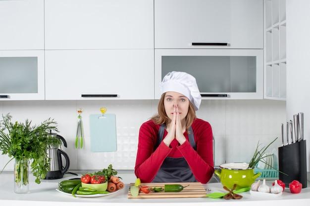 Vooraanzicht vrouwelijke chef-kok in koksmuts en schort