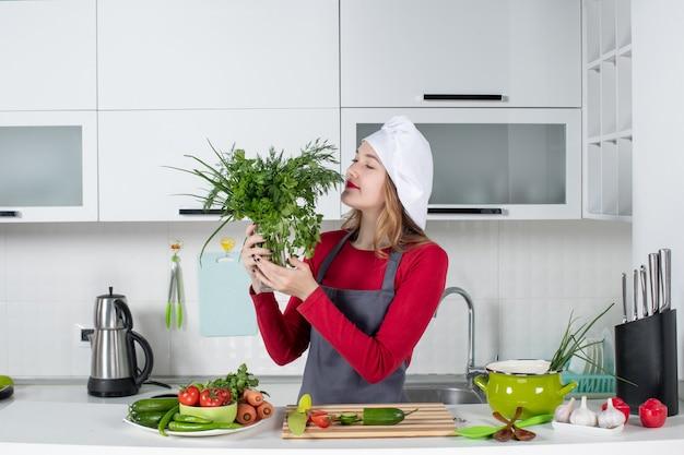 Vooraanzicht vrouwelijke chef-kok in koksmuts ruikende greens