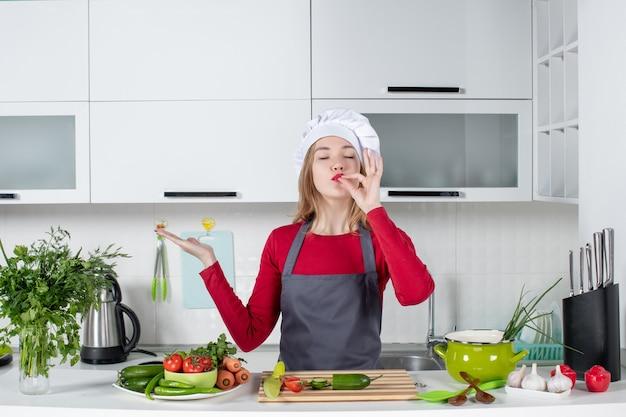 Vooraanzicht vrouwelijke chef-kok in schort die chef-kok kusgebaar maakt