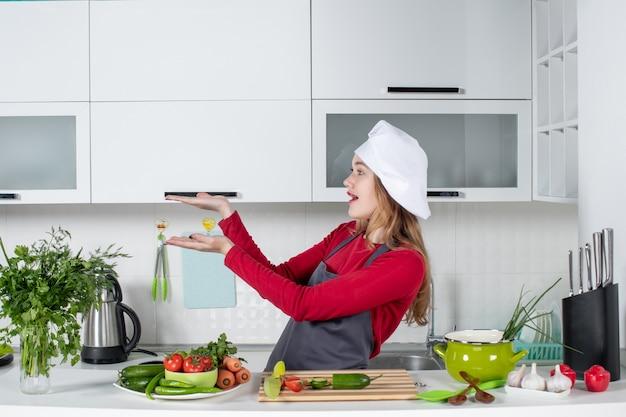 Vooraanzicht vrouwelijke chef-kok in schort die iets toont
