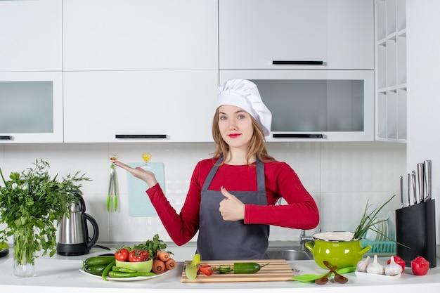 Vooraanzicht vrouwelijke chef-kok in schort duimen omhoog teken maken