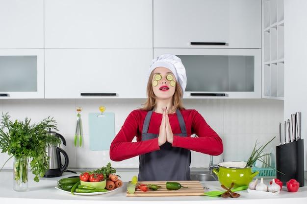 Vooraanzicht vrouwelijke chef-kok in uniform die plakjes komkommer op haar gezicht legt en de handen ineen slaat