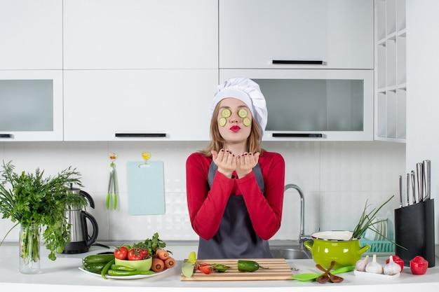 Vooraanzicht vrouwelijke chef-kok in uniform die plakjes komkommer op haar gezicht zet en kus blaast