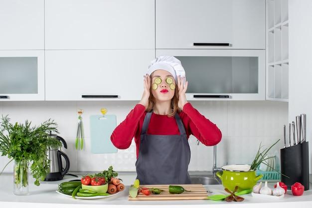 Vooraanzicht vrouwelijke chef-kok in uniform die plakjes komkommer op haar gezicht zet