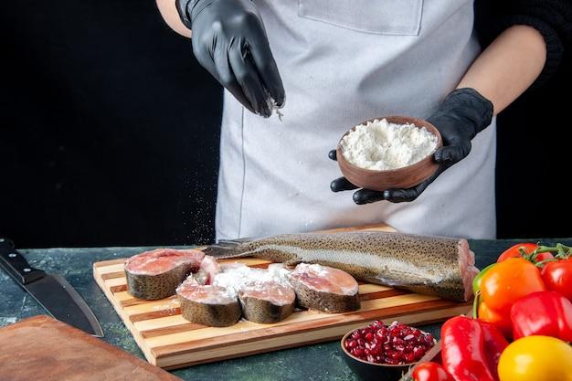 Vooraanzicht vrouwelijke chef-kok met schort die rauwe visplakken bedekt met bloem verse groenten op houten bord meelkom op keukentafel