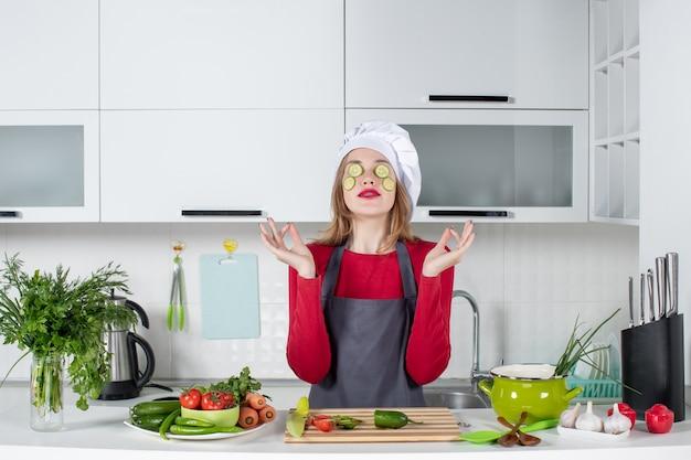 Vooraanzicht vrouwelijke chef-kok met speciaal handgebaar die plakjes komkommer op haar gezicht zet