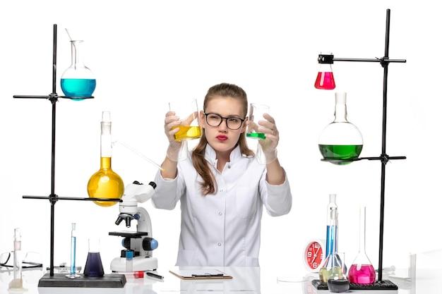 Vooraanzicht vrouwelijke chemicus in medisch pak bedrijf kolven met oplossingen op witte achtergrond chemie pandemie gezondheid covid