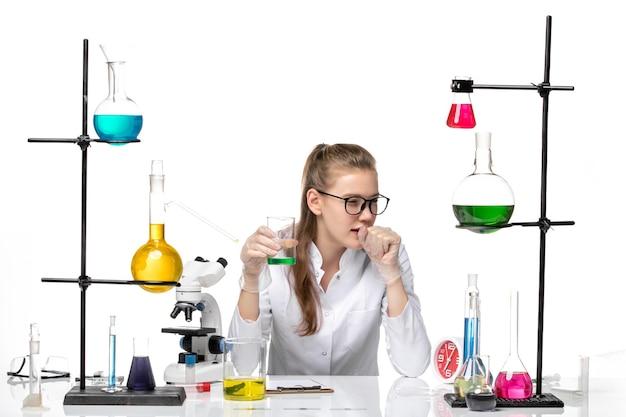Vooraanzicht vrouwelijke chemicus in medisch pak controleren geur van oplossing en hoesten op witte achtergrond chemie pandemie gezondheid covid