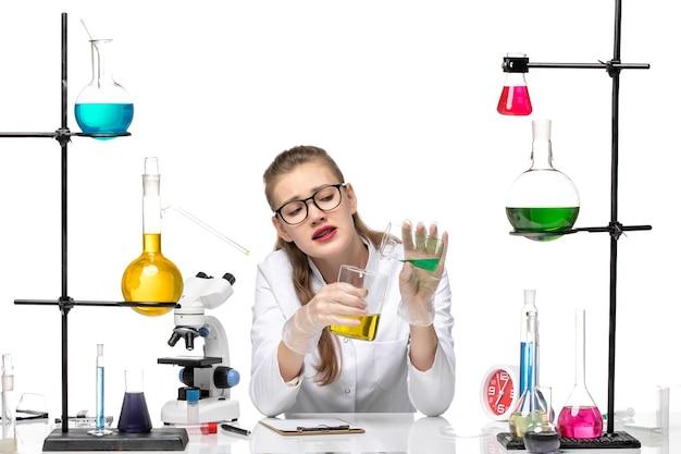 Vooraanzicht vrouwelijke chemicus in medisch pak dat verschillende oplossingen op witte achtergrond mengt chemie pandemie gezondheid covid