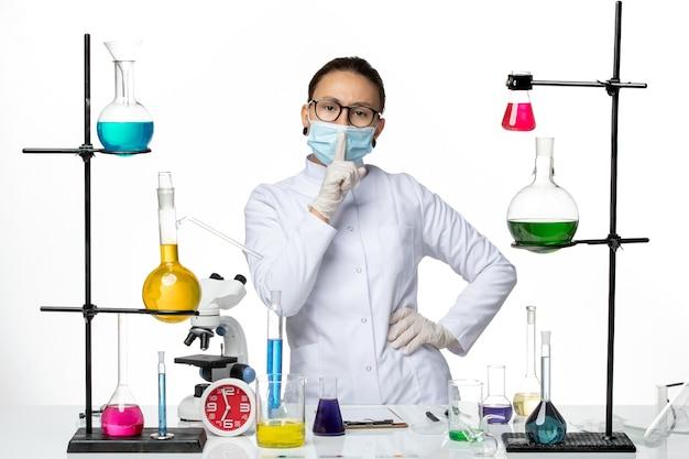 Vooraanzicht vrouwelijke chemicus in medisch pak dragen masker staande op lichte witte achtergrond virus chemie lab covid-splash