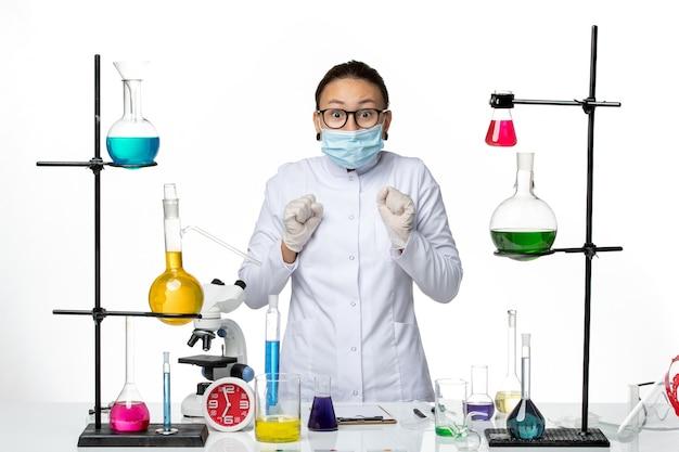Vooraanzicht vrouwelijke chemicus in medisch pak en het dragen van masker staande op een witte achtergrond virus chemie lab covid-splash