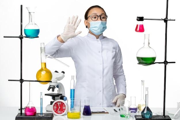 Vooraanzicht vrouwelijke chemicus in medisch pak en masker zwaaien naar iemand op witte achtergrond virus chemie lab covid-splash