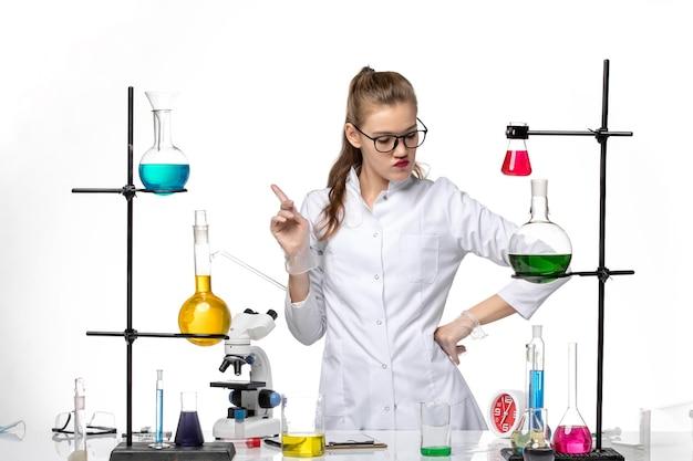 Vooraanzicht vrouwelijke chemicus in medisch pak in werkproces met oplossingen op wit bureauchemie pandemisch covid-virus